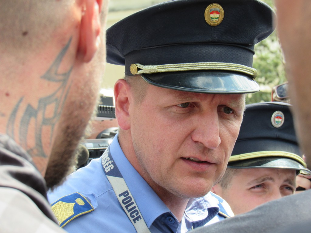 Egy rendőrkapitány a huligán kinézetű, névtelen biztonsági őrökkel konzultál...számára is úgy tűnik, hogy kellemetlen lehet ez a helyzet. Fotó: C. Adam